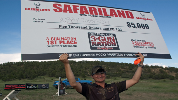 Picture of a young man in a ball cap and dark t-shirt holding a large placard showing his winnings