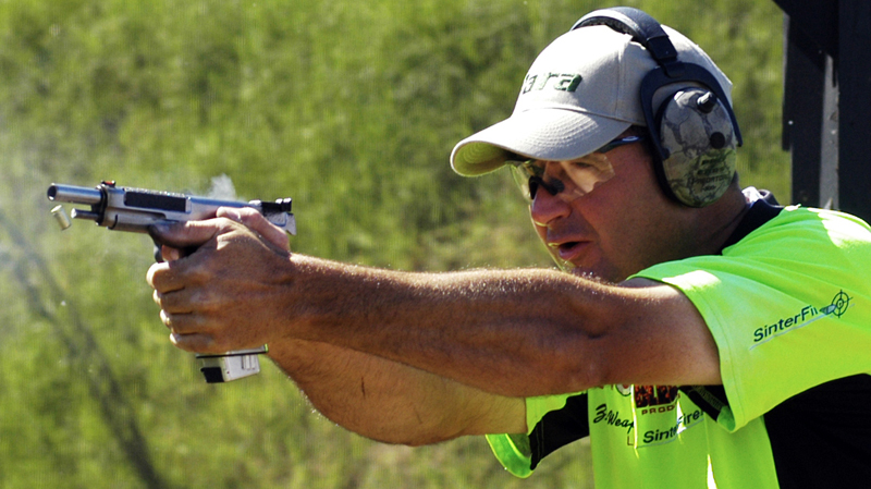 Todd Jarrett, in white ball cap and neon yellow shirt shows off his shooting skills at the USPA Steel Challenge