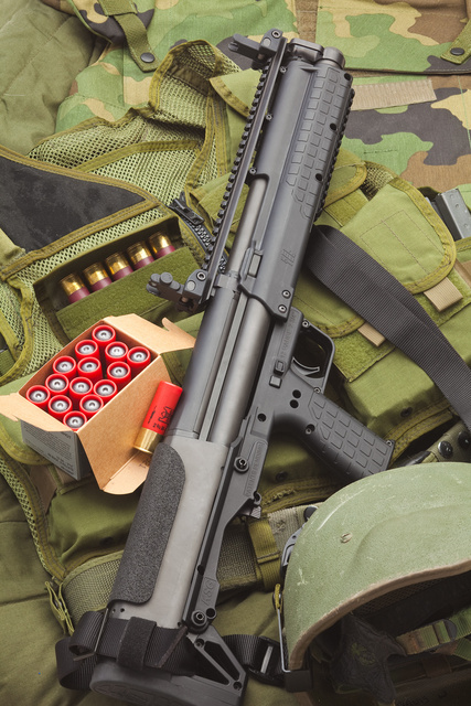 The Kel-Tec KSG and a box of ammo lying on a background of camo clothing.