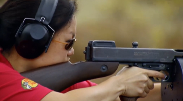 Young woman in black ear protection and red shirt practices her skill with a Tommy gun