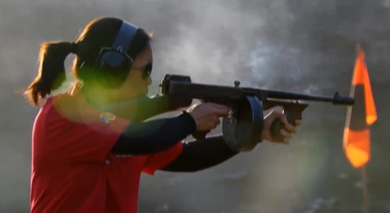 Dark haired woman in red shirt and black ear protection practices her skills shooting a black Tommy gun