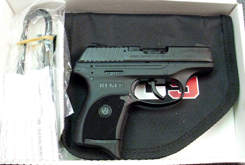 Black Ruger LC9, barrel pointed to the right, in a box
