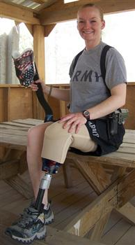 Young woman in a gray shirt and shorts with artificial leg gets ready to compete.