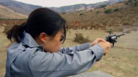 Black haired woman in light blue-gray shirt shoots a black pistol with hills and grass surrounding her