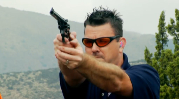 dark haired man in medium blue shirt shirts his 44 mag, with handgun facing the viewer and trees and mountains in the background