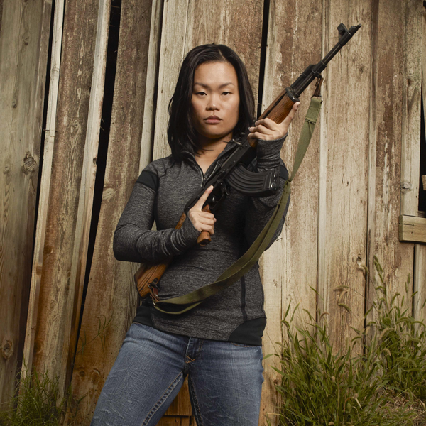 Young woman in gray sweater and jeans shows off her favorite gun with a brown fence behind her