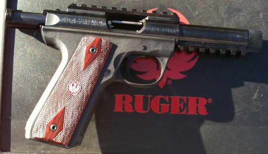 Ruger 22/45 with light brown grip, factory installed rails and a threaded barrel on black background with Ruger name and logo in red