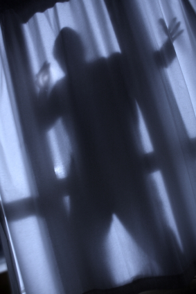 Shadow of a burglar through the sheer curtains of the window.