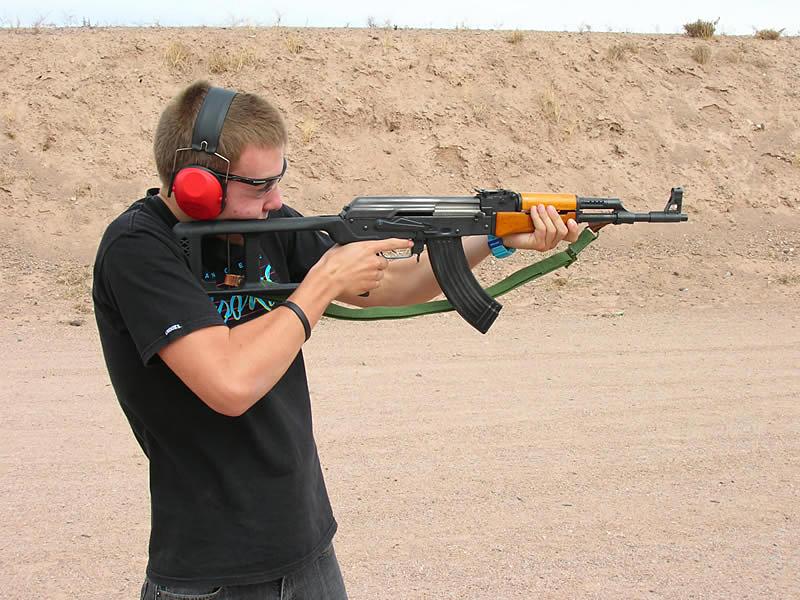 Teenage male shooting an AK-47