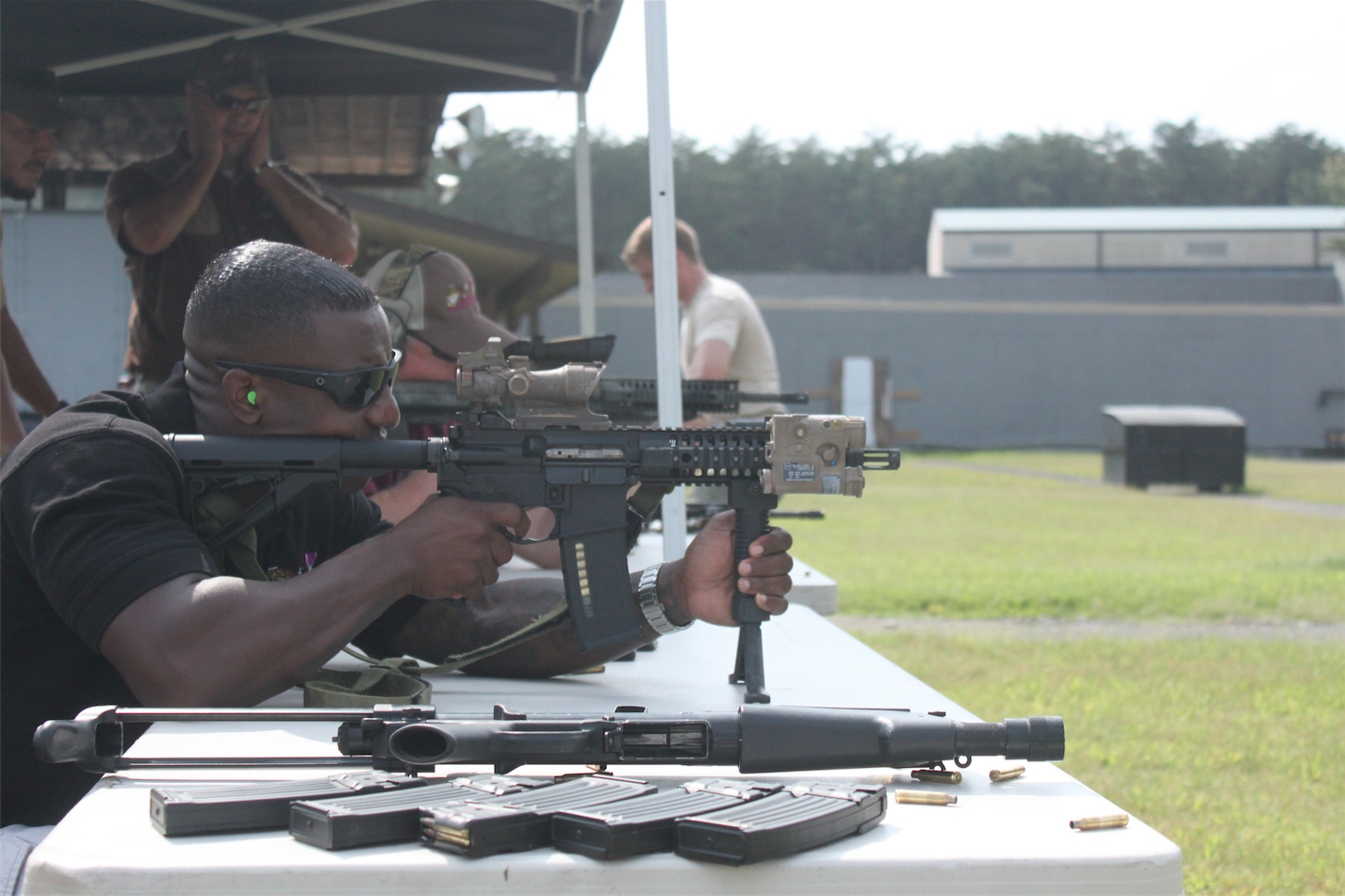 A man is shooting a rifle at an outdoor gun range.