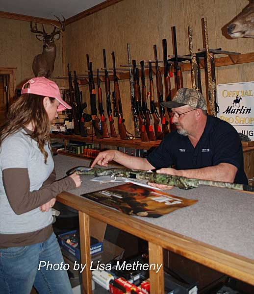 Woman with pink hat shopping at gun counter