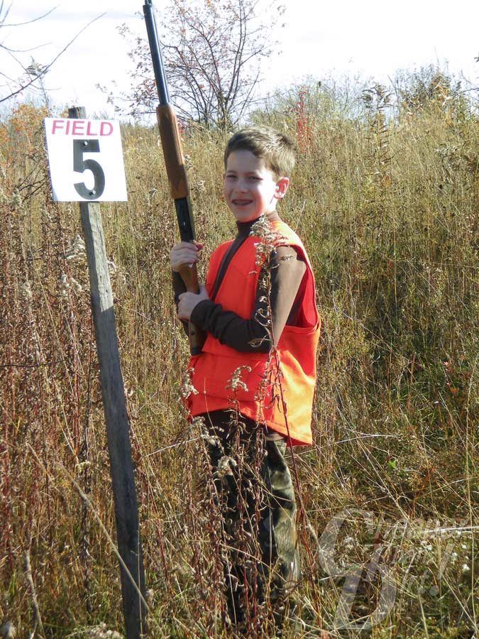youth wearing orange safety vest and shotgun