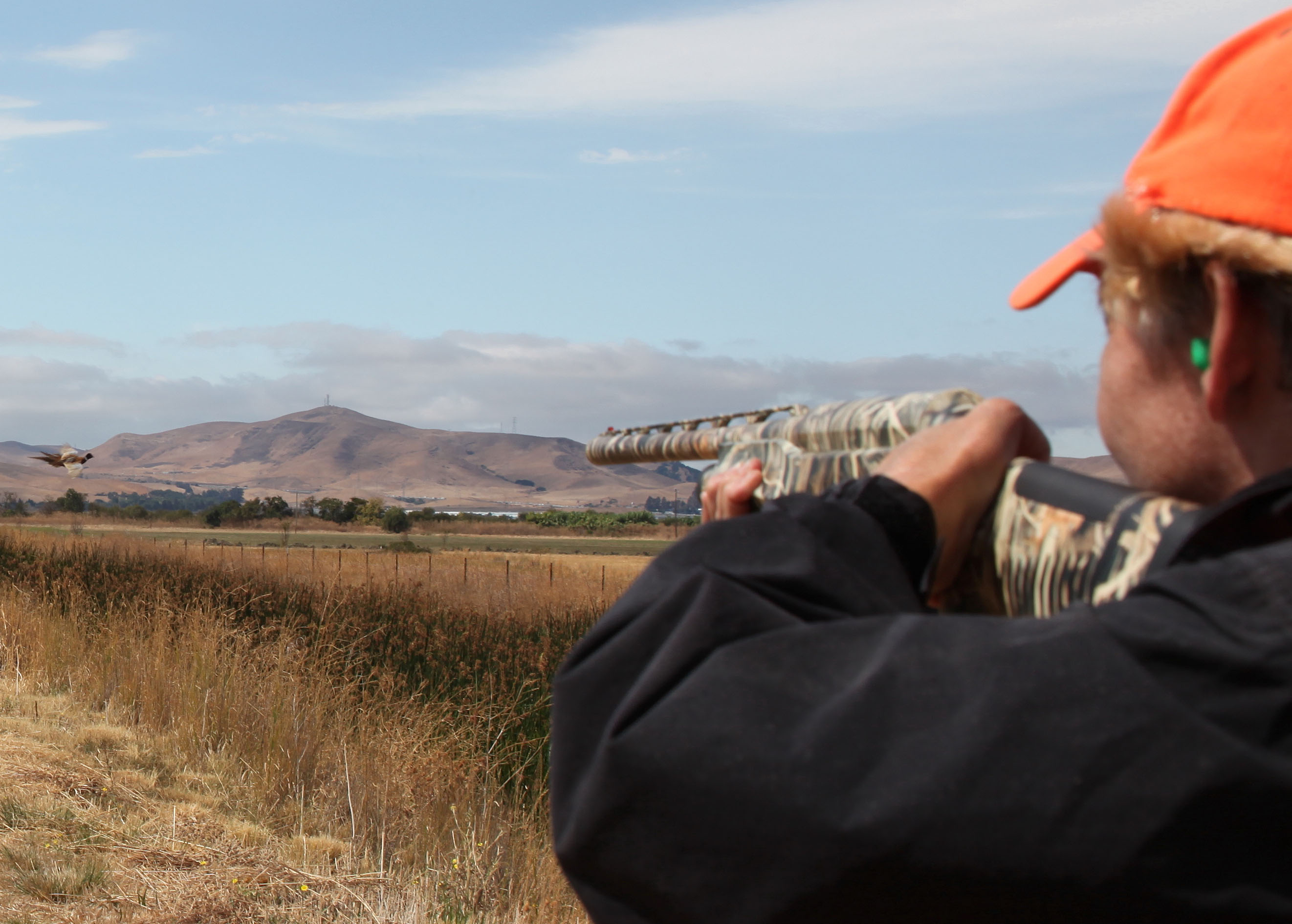 Man holding a camo shotgun in the field