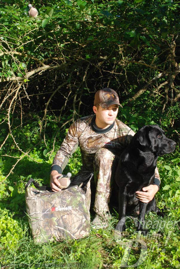 Hunter wearing camo with lab and dove decoy.