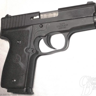 A black Kahr K9, muzzle pointing right, on a gray to white background. The focus is on the excellent machine work.