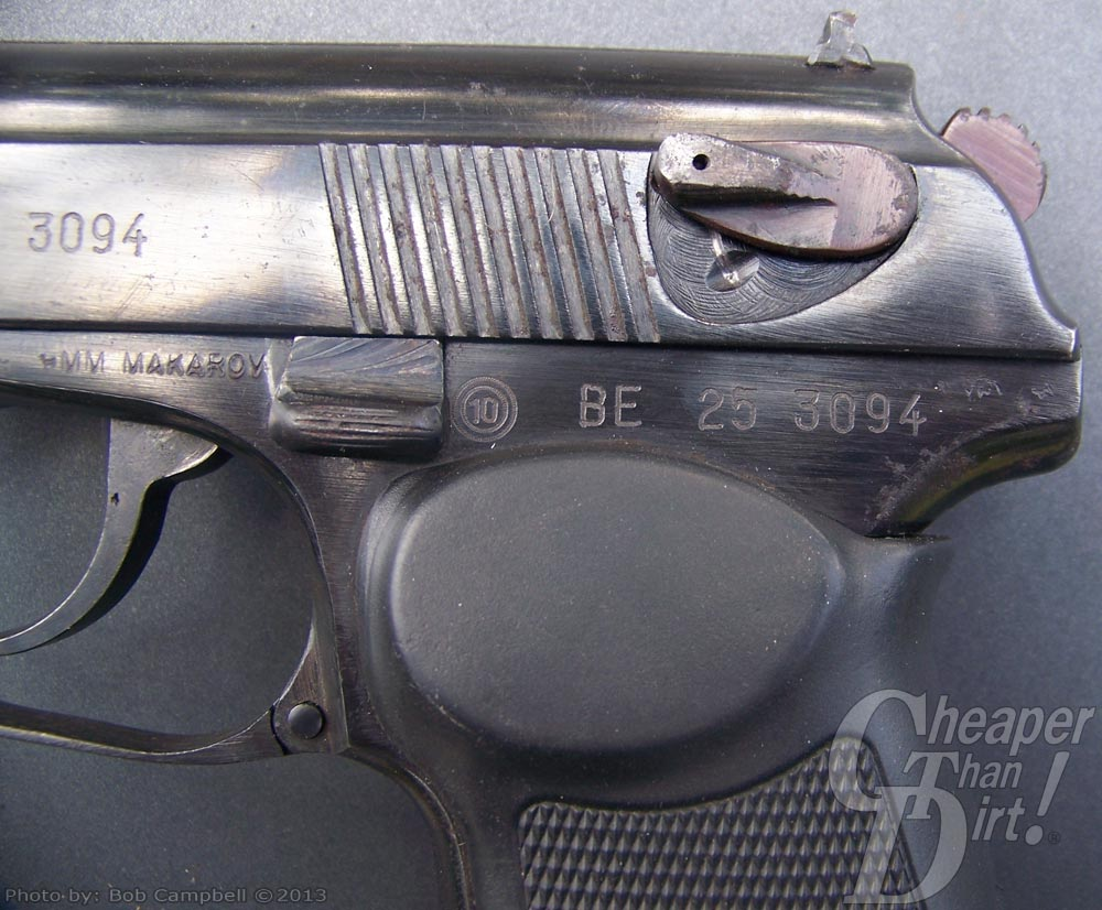 A well-used Makarov laying on it's side on a gray background, with the safety on