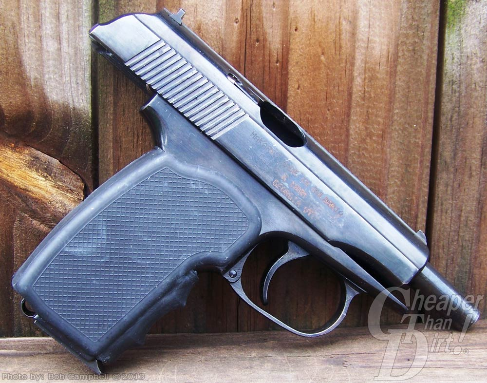 A Makarov with muzzle pointed downward on a wood panel background with the slide locked back and fitted with Pearce grips