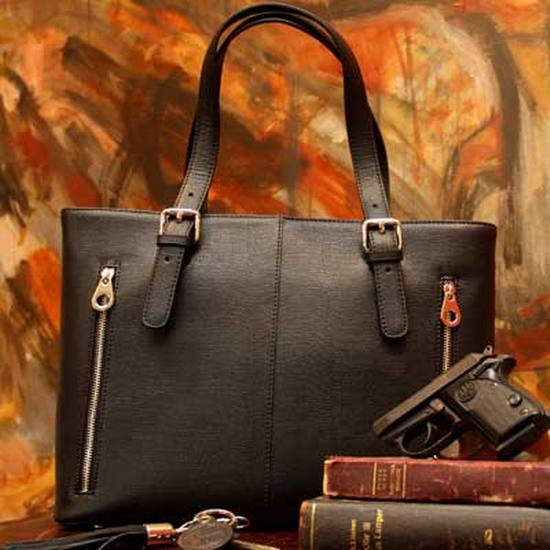 Black purse with gun on top of 2 old books on a printed leaf-style background.