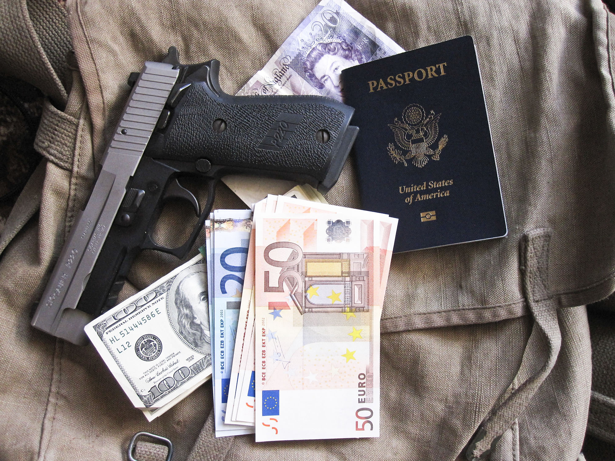 Picture shows a gun, a United States passport and foreign currency.
