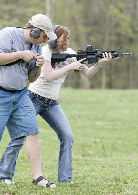 Picture shows a woman learning how to shoot an AR-15 rifle.