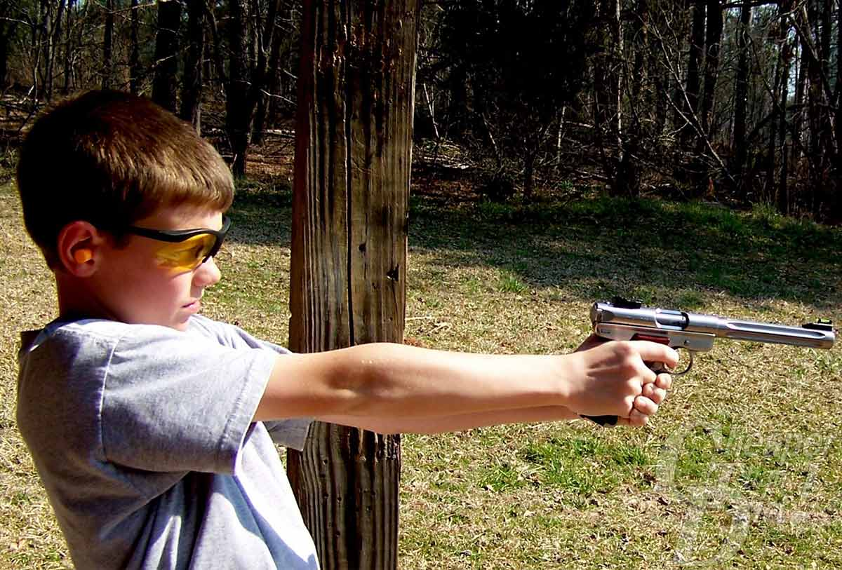 A boy in a gray t-shirt and safety glasses using a .22 LR to practice his shooting skills. The background is a green and brown grassy area with a wooded area.