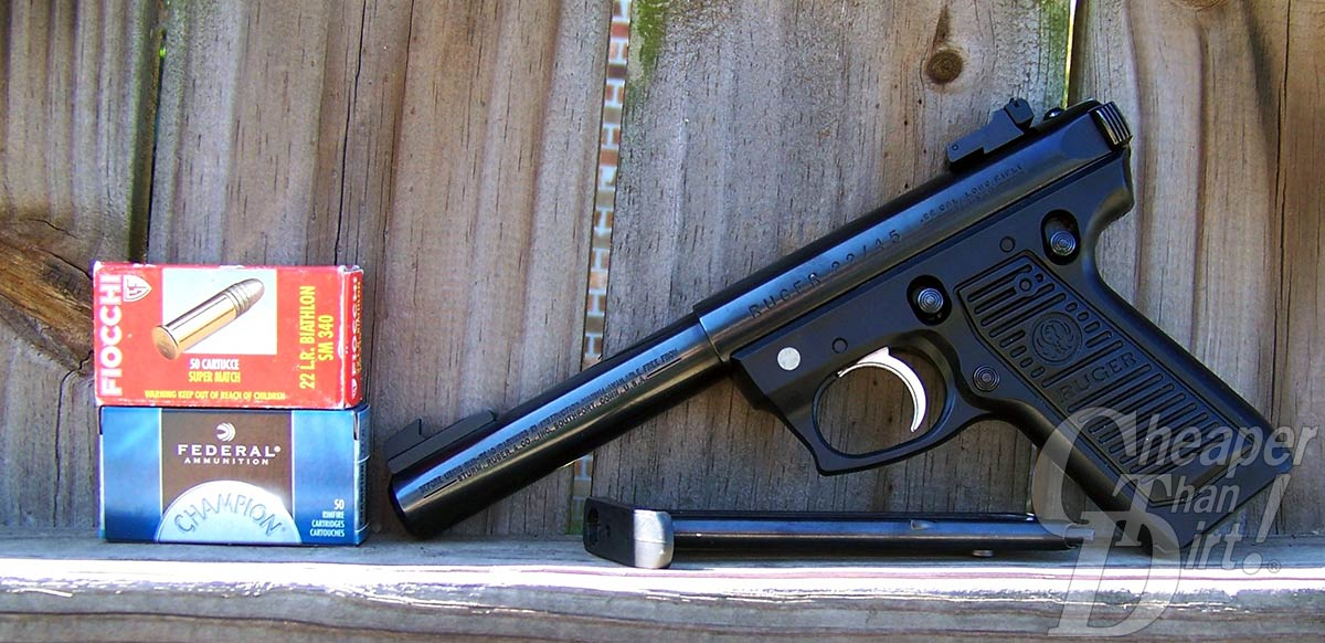 A black Ruger .22/45, barrel pointed down, with 2 boxes of ammunition against a wooden background.