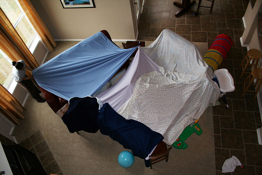 Picture shows a woman setting up a living room fort made with sheets and chairs.