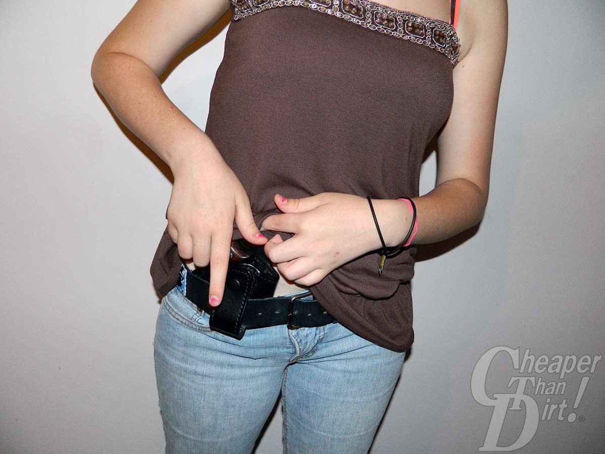 A young woman in blue jeans and a brown shirt with a .38 in a black Blackhawk holster attached to a black belt.