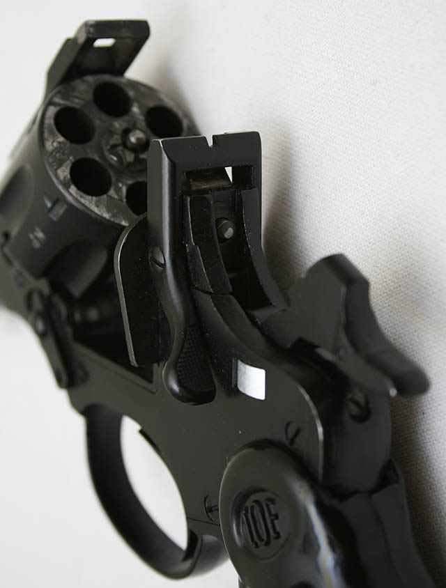 Picture shows a close up of the back of a black revolver with the cylinder open, empty.