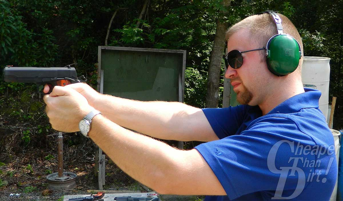 A young man with a beard in a blue shirt with green hearing protection shoots the Para Ordnance Commander.45.
