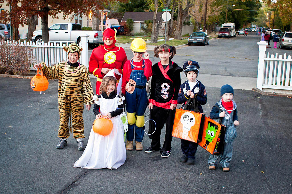 Picture shows a group of children in costumes, trick or treating on Halloween.