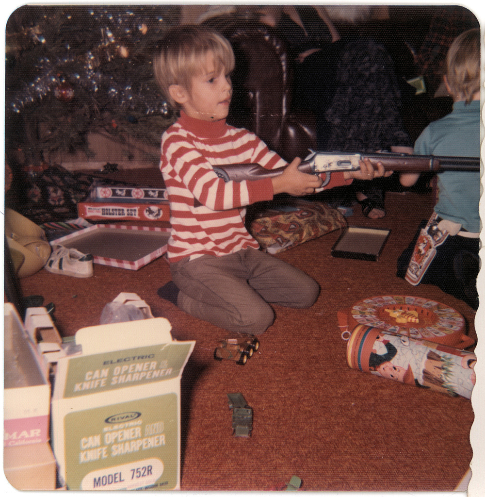 Vintage picture of a little boy sitting by the Christmas tree holding a lever-action rifle.