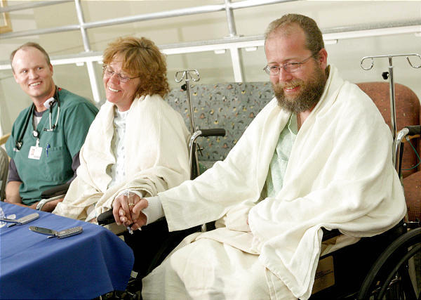 Picture shows Tom and Tamitha Garner holding hands, covered in blankets after being stuck in the snow for 12 days.