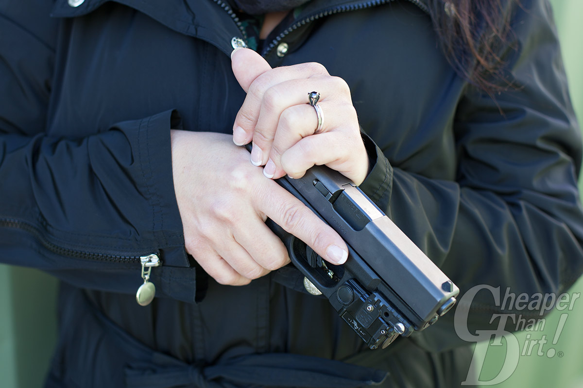 Close up of a woman holding a Glock handgun demonstrating how to wrap one's fingers around the slide in order to rack it.