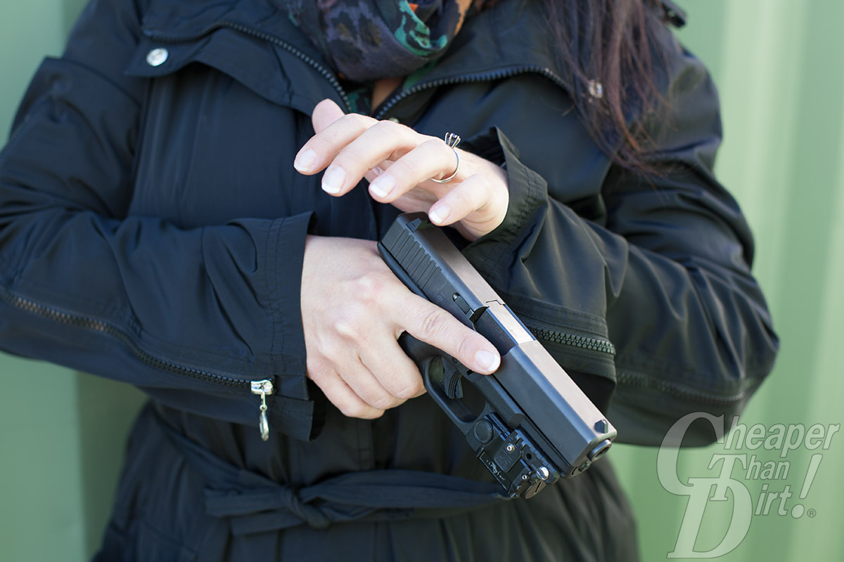 Close up of a woman letting go of the slide on a Glock handgun.