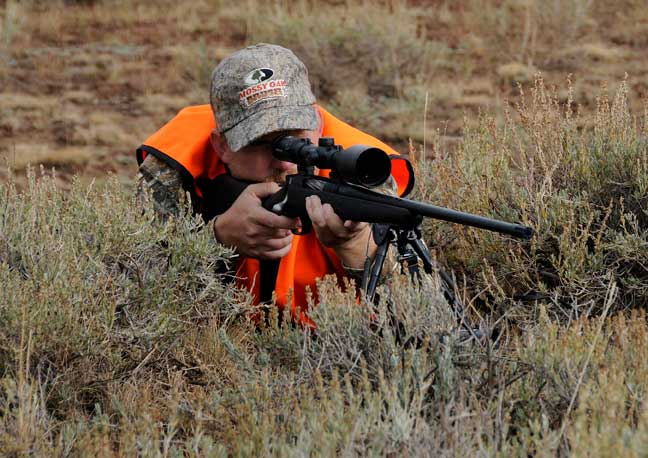 HUnter wearing blaze orange shooting a McMillan rifle from a prone position through sage brush.