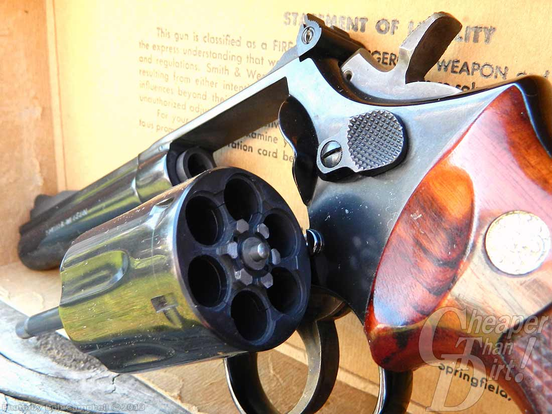 Smith and Wesson revolver with chamber open and wood grain grip, pointed downward on pale yellow background with partial wording showing.