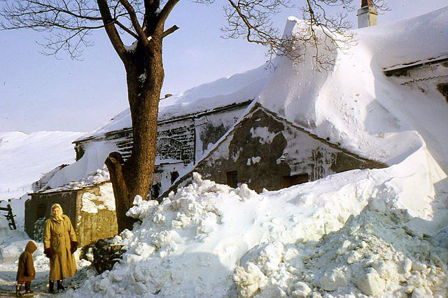 Picture shows an old farm house with snow piled to the roof.