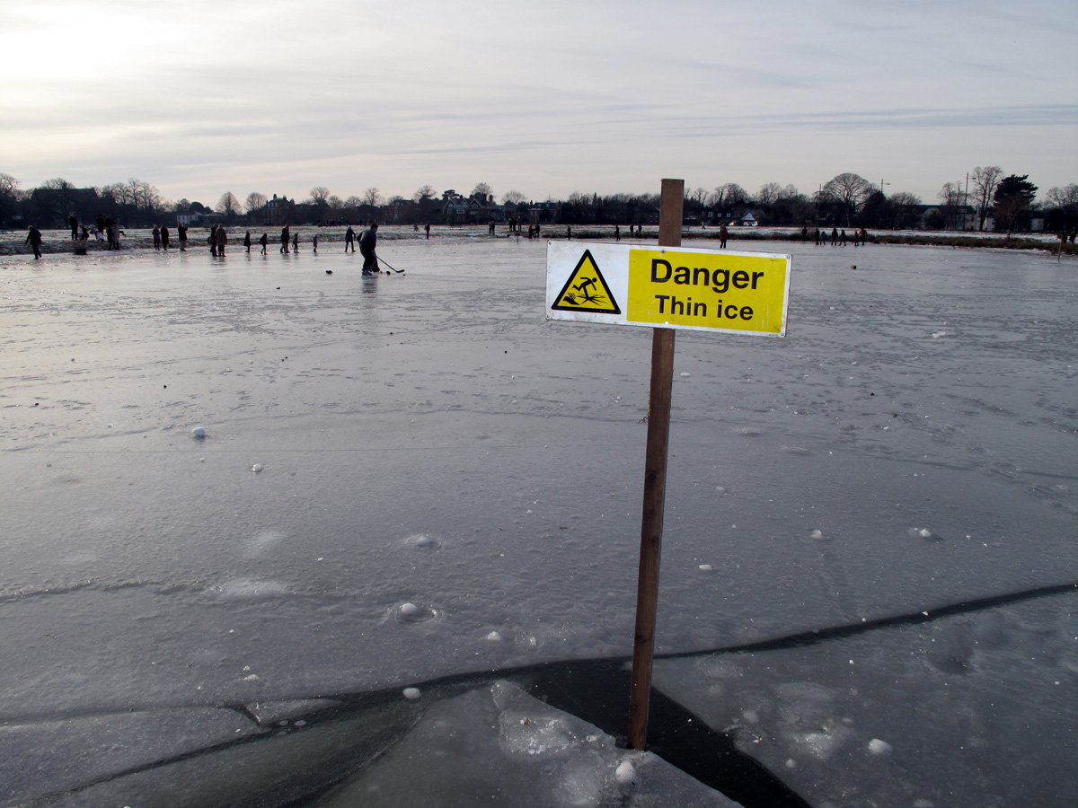 """Picture shows a frozen lake, people skating in the distance and a sign that reads, """"Danger. Thin ice."""""""
