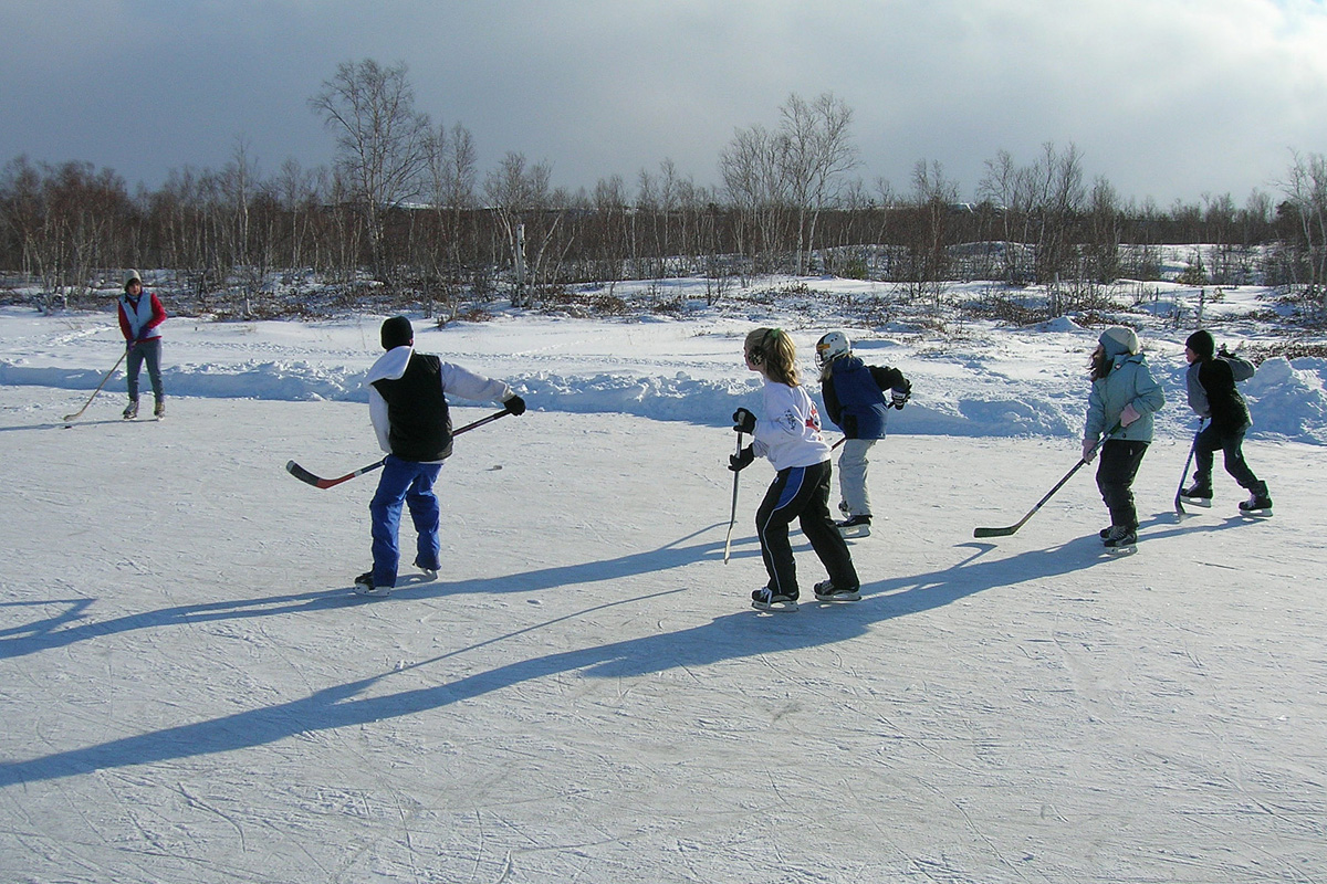 Picture shows a group of children playing ice hockey on a frozen pond covered in a layer of white ice and snow.