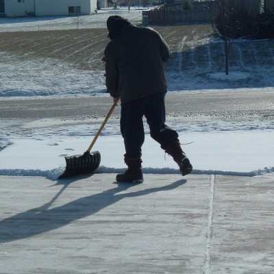 Person from the back bundled up for winter shoveling snow on a driveway.