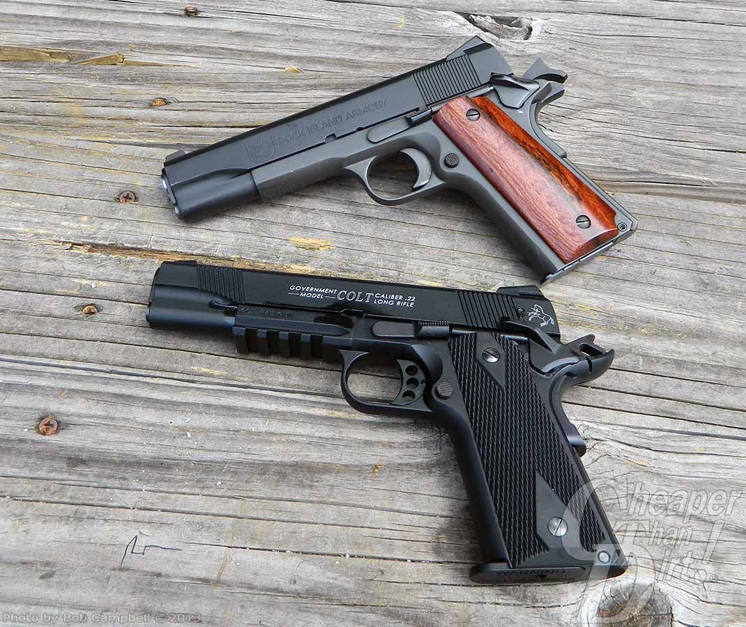 2 stacked pistols, a Rock Island Armory 1911 with a brown wood-grained grip and the Colt .22 in all black, both barrels pointing to the left on a gray weathered board background.