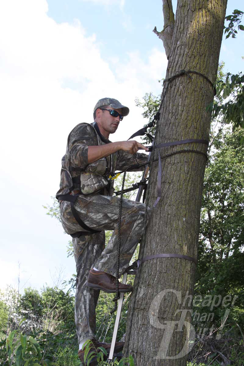 Hunter in tree hanging a stand using a safety harness