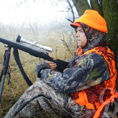 Hunter leaning against a tree with rifle on bipod