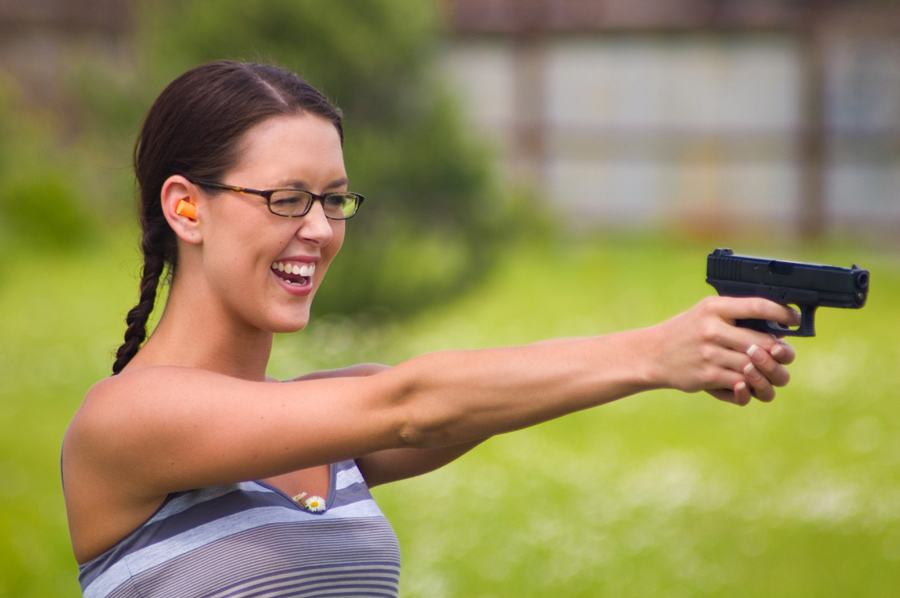 Picture shows a young woman with a giant smile on her face shooting a small, black handgun.
