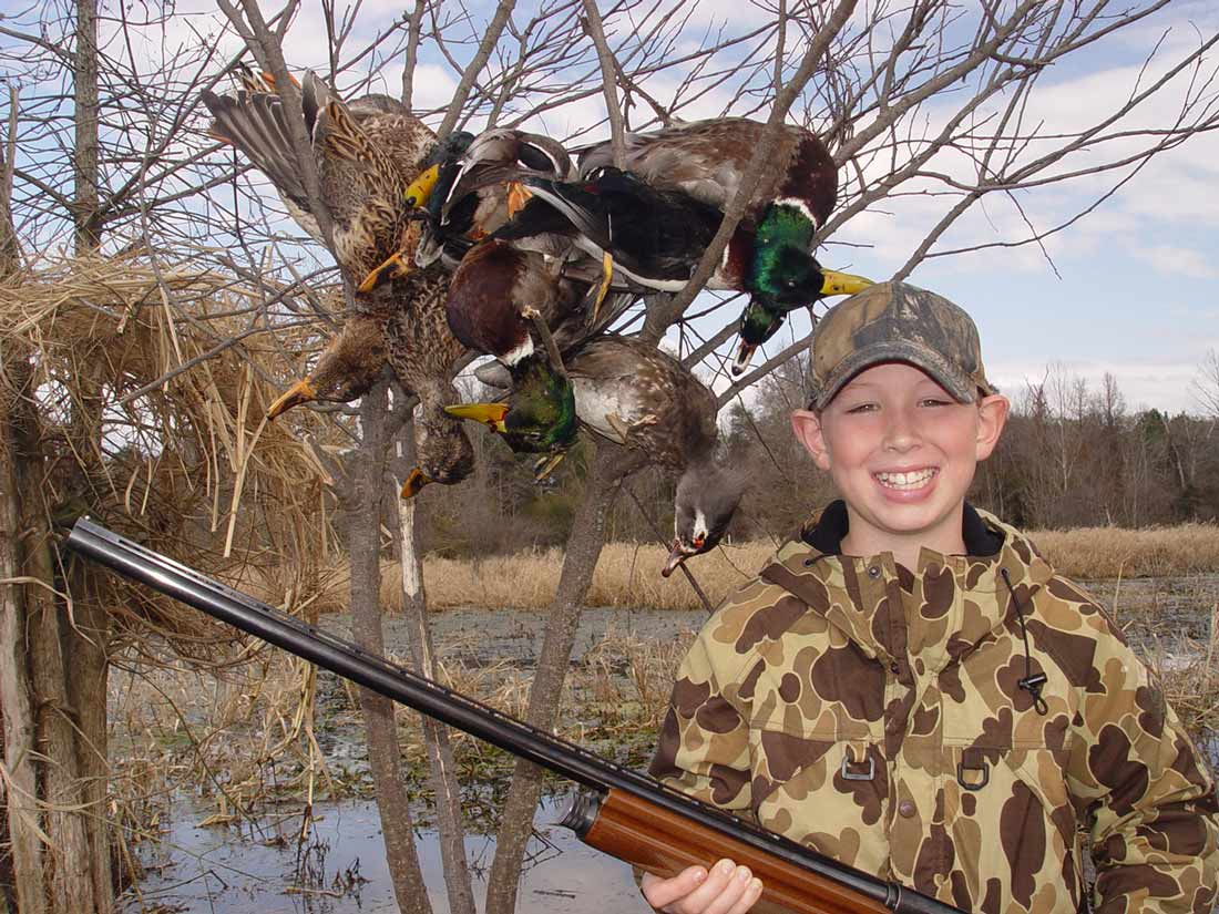 Picture shows a little boy smiling, holding his shotgun with downed ducks in the background.