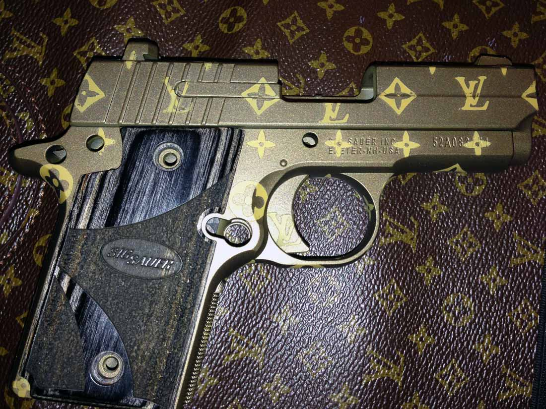 Picture shows a SIG Sauer pistol Cerakoted in custom Louis Vuitton pattern.
