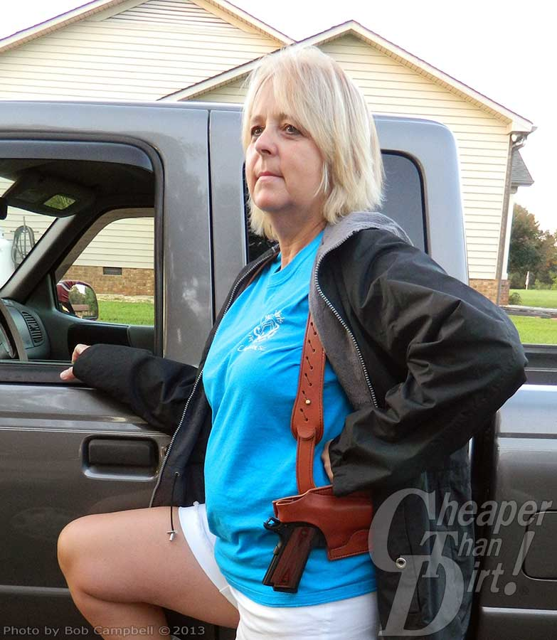 Blond haired woman in a turquoise shirt and white shorts shows off the Para Commander .45 while leaning against a gray truck.