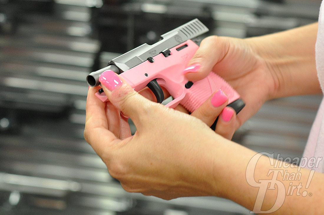 Picture shows a close up of a woman with bright pink fingernails holding a pink and silver Taurus small semi-automatic handgun.