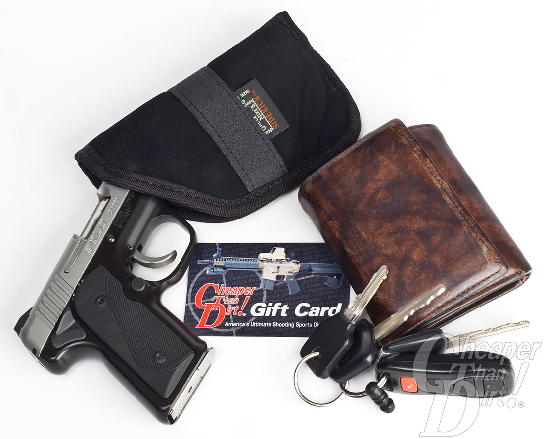 The picture shows a Kimber Solo handgun, holster, car keys, a brown wallet and a Cheaper Than Dirt gift card.